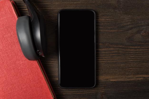 Teléfono móvil, libro y auriculares en primer plano. vista superior del fondo de madera.