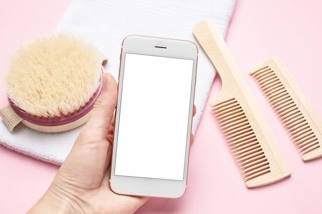 Teléfono móvil en mano y cepillo de dientes de madera ecológica, peine, cepillo para masaje seco en rosa