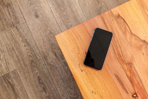 Teléfono móvil con maqueta de pantalla en blanco sobre fondo de mesa de madera