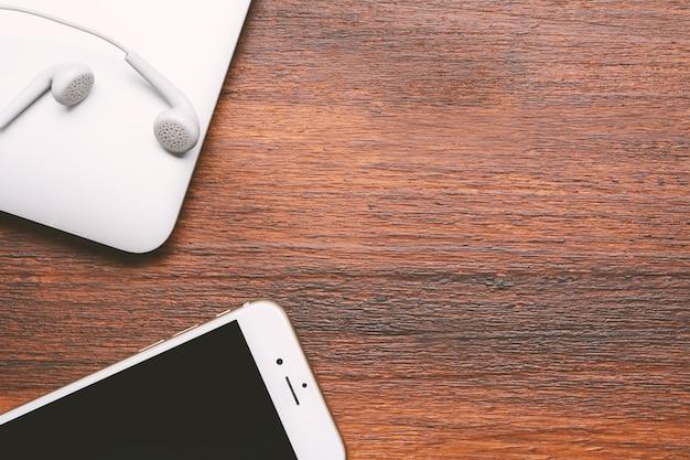 Teléfono móvil, ordenador portátil y auricular blanco con copyspace.
