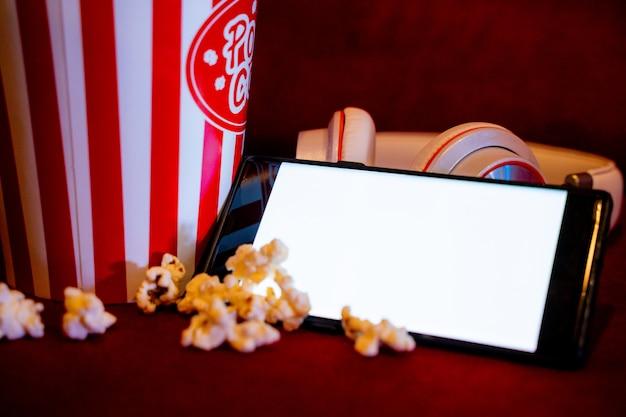 Teléfono móvil con pantalla blanca brillante vacía con cubo de palomitas de maíz en el sofá rojo