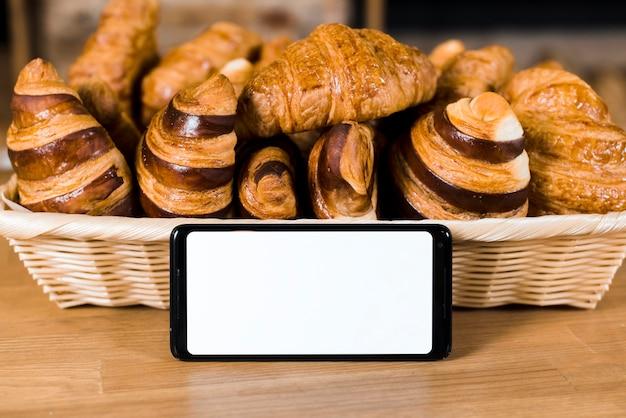 Teléfono móvil con pantalla blanca cerca de la canasta llena de croissant horneado en mesa de madera