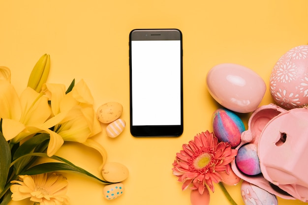 Teléfono móvil con pantalla en blanco blanco decorado con lirio; flor de gerbera y coloridos huevos de pascua sobre fondo amarillo