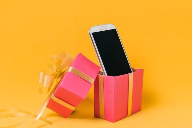 Teléfono móvil con pantalla en blanco en caja de regalo rosa.