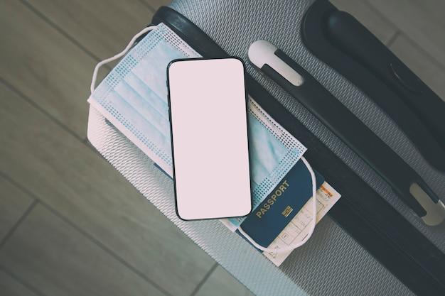 El teléfono móvil con pantalla en blanco para certificado de vacunación digital y pasaporte, máscara y boleto en la maleta.
