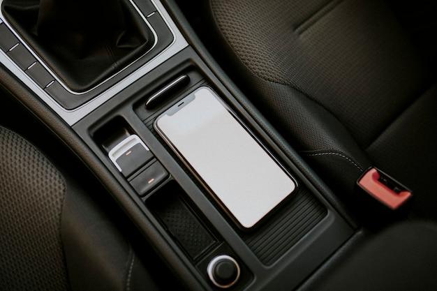 Teléfono móvil de pantalla en blanco dentro de un coche