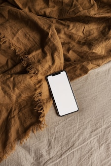 Teléfono móvil de pantalla en blanco sobre una manta marrón, beige