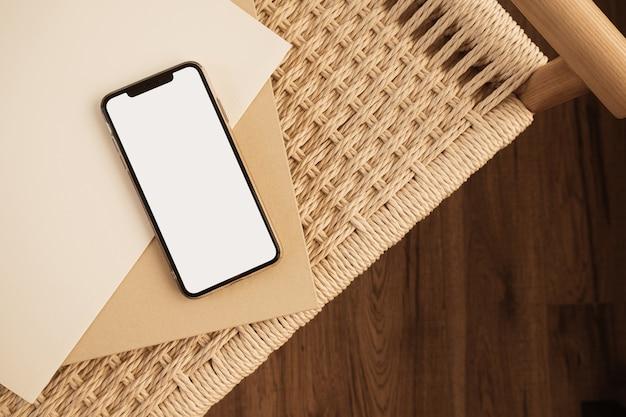 Teléfono móvil de pantalla táctil en blanco sobre fondo de mimbre. endecha plana, vista superior
