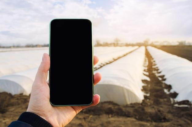 Teléfono móvil con una pantalla vacía en blanco sobre invernaderos agrícolas