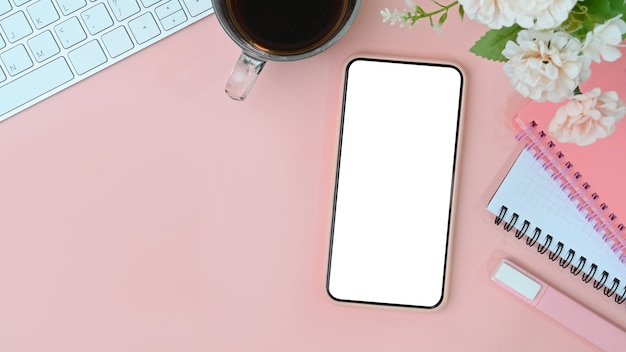 Teléfono móvil con pantalla vacía, taza de café, flores y cuaderno sobre fondo rosa pastel.