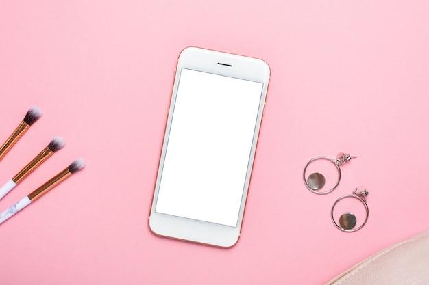 Teléfono móvil con pinceles de maquillaje y aretes en mesa de color rosa pastel en estilo plano. escritorio de belleza femenina.