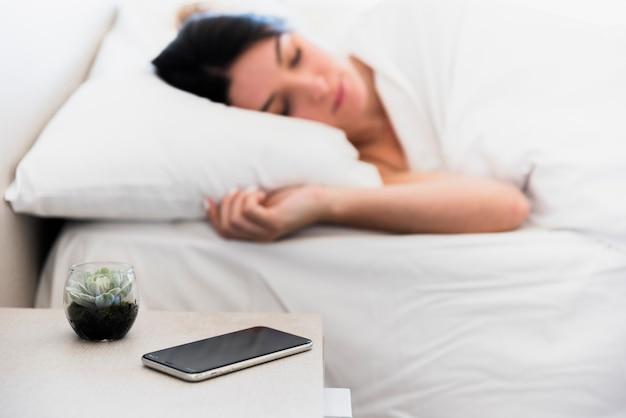 Teléfono móvil y planta de cactus en la mesita de noche cerca de una mujer joven que duerme en la cama