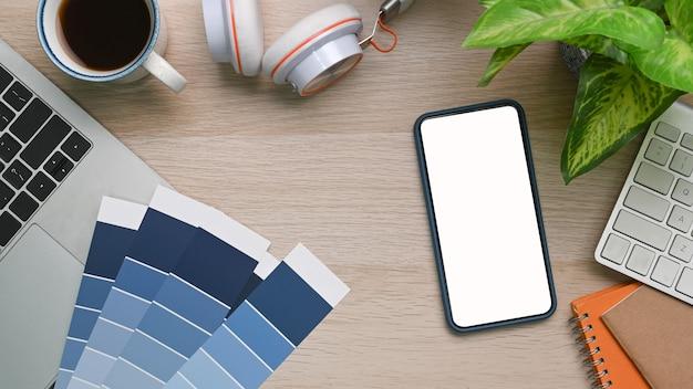 Teléfono móvil, portátil, auriculares y taza de café en un escritorio de madera