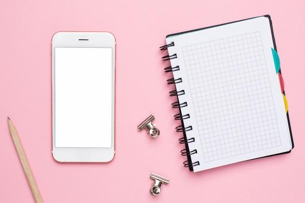 Teléfono móvil y portátil en una jaula sobre un fondo rosa