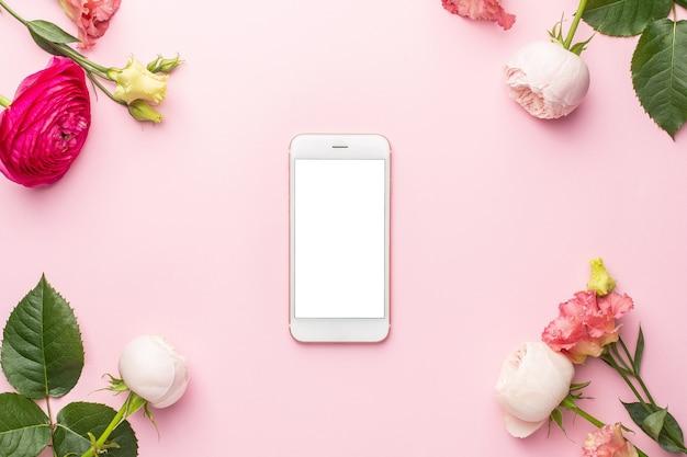 Teléfono móvil y ramo de flores rosas ranunculi
