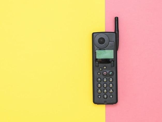 Teléfono móvil retro con antena externa en superficie rosa y amarilla. medios de comunicación retro. tecnología del pasado.