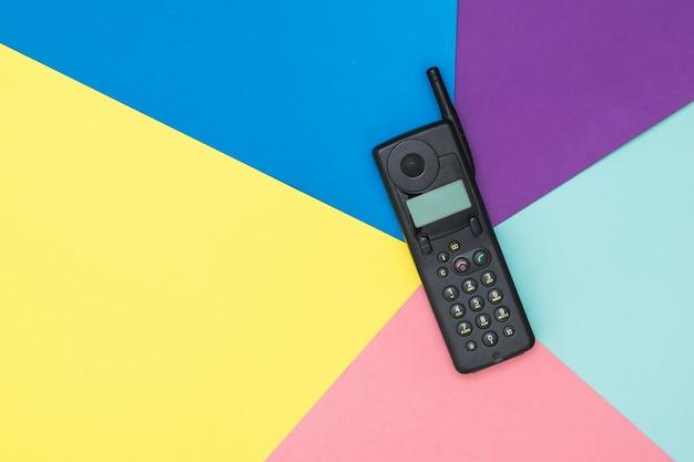 Teléfono móvil retro con antena en superficie colorida