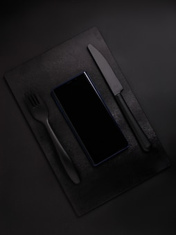 Teléfono móvil en tablero negro con tenedor negro y cuchillo negro sobre fondo negro, vista superior