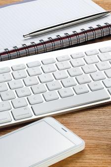Teléfono móvil, teclado de computadora, bolígrafo y bloc de notas para notas.