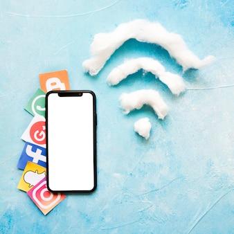 Teléfono móvil y vívido icono de redes sociales al lado del símbolo de wi-fi hecho de algodón