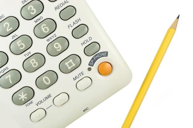 Teléfono de oficina con lápiz amarillo sobre blanco