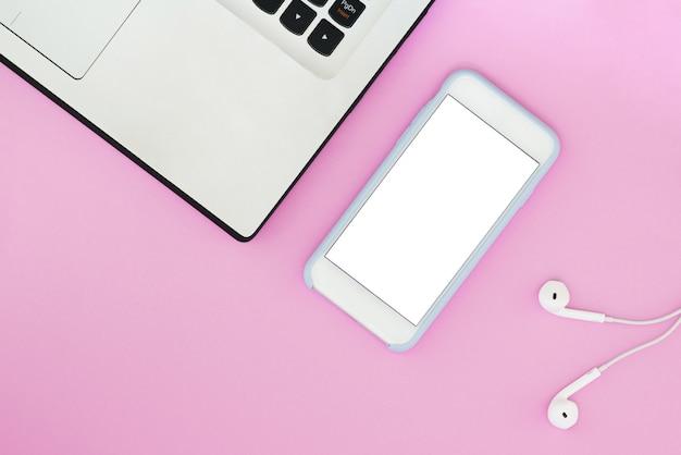 Un teléfono con una pantalla blanca, una computadora portátil y auriculares sobre un fondo rosa y con un lugar para el texto.