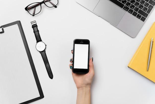 Teléfono con pantalla en blanco copia espacio en mano femenina. escritorio de oficina blanco plano con suministros, vista superior fondo del espacio de trabajo.