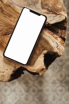Teléfono de pantalla en blanco con maqueta de espacio de copia vacía en taburete de madera maciza y alfombra. endecha plana