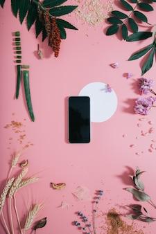 Teléfono con pantalla clara y forma de círculo blanco en flores en pared rosa. endecha plana. vista superior