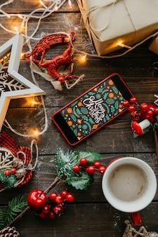 Teléfono con pantalla navideña y café con leche sobre la mesa