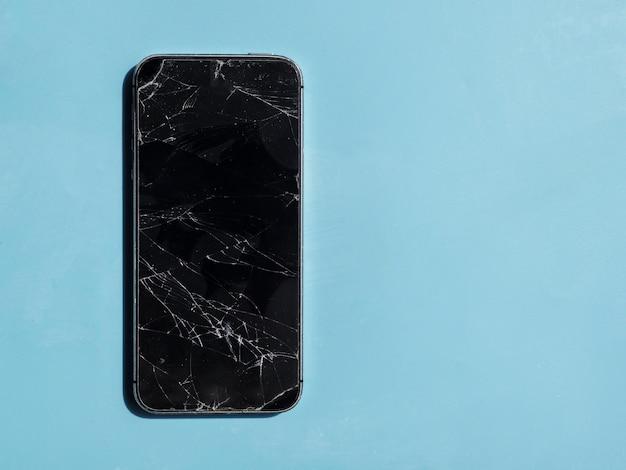 Teléfono con pantalla rota sobre fondo azul