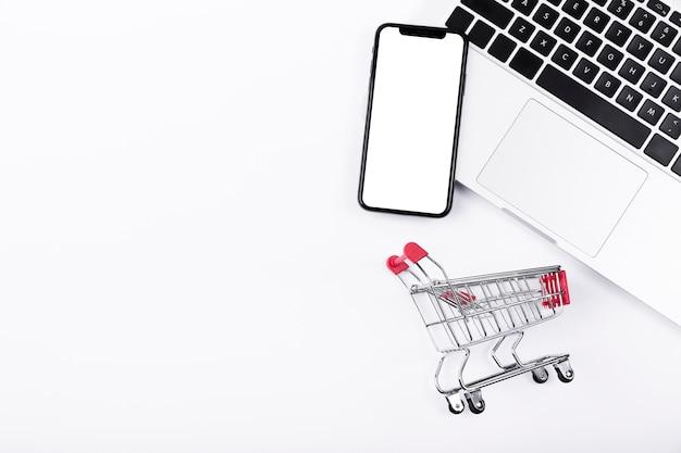 Teléfono en la parte superior de la computadora portátil con carrito de compras