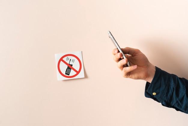 Un teléfono prohibido etiqueta engomada del símbolo de signo prohibido en la pared aislada