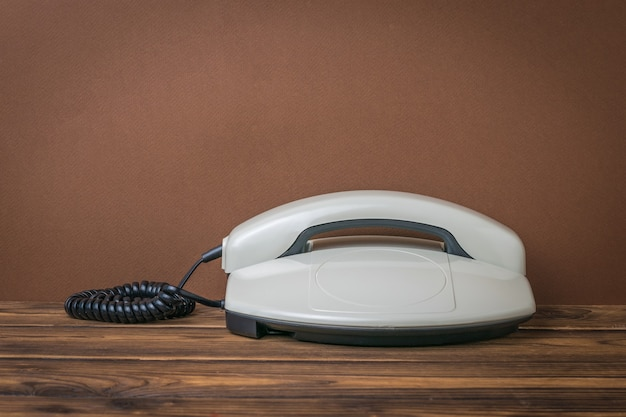 Teléfono retro gris sobre una mesa de madera sobre un fondo marrón. medios de comunicación retro.