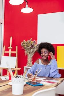 Teléfono rojo. elegante mujer joven con bonitos accesorios sosteniendo su teléfono rojo mientras llama a un amigo
