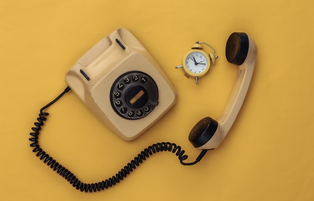 Teléfono rotatorio retro y mini despertador sobre un fondo amarillo.