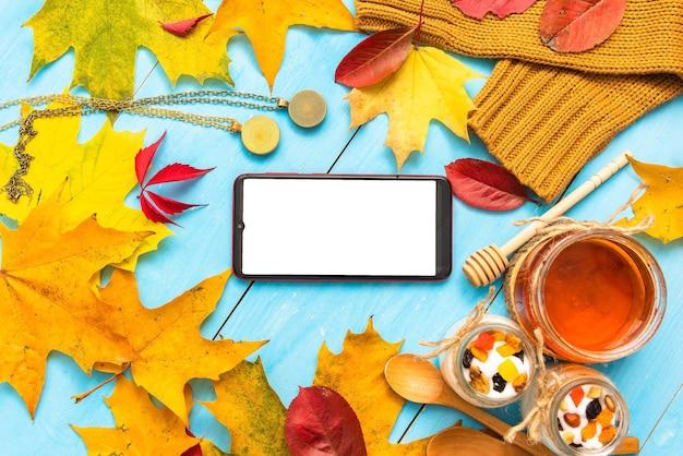 Teléfono sobre la mesa con café de la mañana y miel. en otoño.