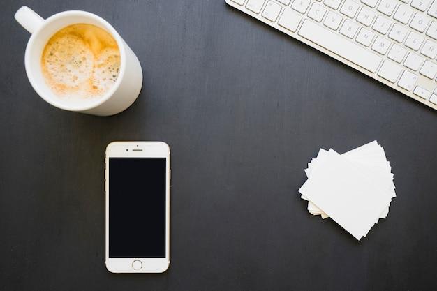 Teléfono, tarjetas, café y teclado