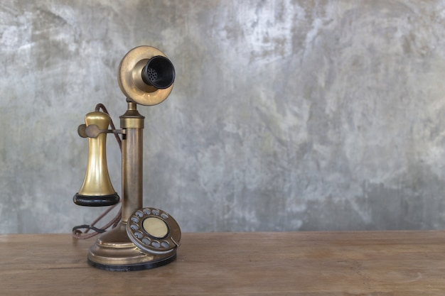 Teléfono del vintage en la tabla de madera con el fondo de la pared del cemento, imagen con el espacio de la copia.