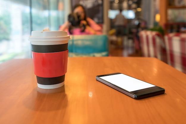 Teléfonos móviles y tazas de café para llevar en la mesa de la cafetería.
