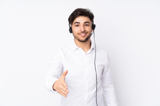 Telemarketer hombre árabe que trabaja con un auricular aislado en la pared blanca apretón de manos después de un buen trato