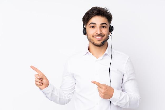 Telemarketer hombre árabe que trabaja con un auricular aislado en la pared blanca apuntando con el dedo hacia un lado