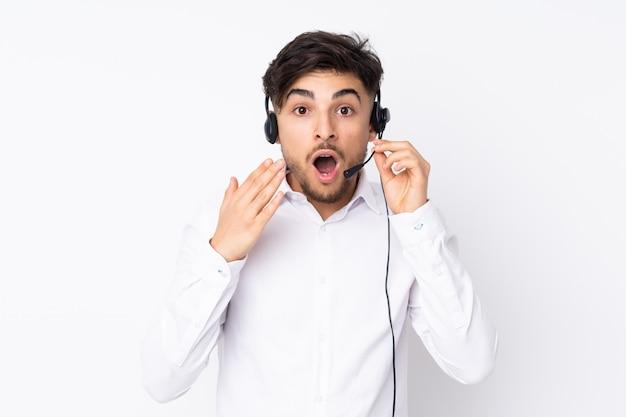 Telemarketer hombre árabe que trabaja con un auricular aislado en la pared blanca con expresión facial sorpresa