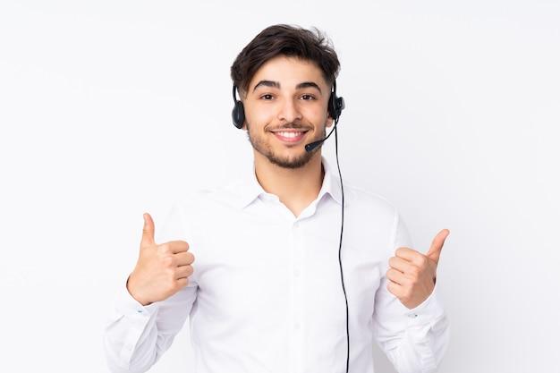 Telemarketer hombre árabe que trabaja con un auricular en la pared blanca dando un gesto de aprobación