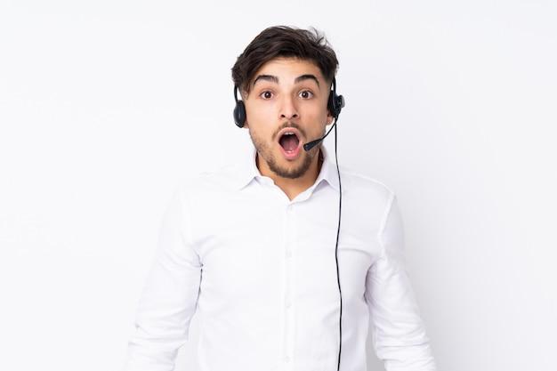 Telemarketer hombre árabe que trabaja con un auricular en la pared blanca con expresión facial sorprendida