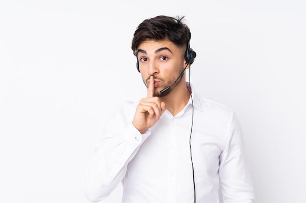Telemarketer hombre árabe que trabaja con un auricular en la pared blanca haciendo gesto de silencio