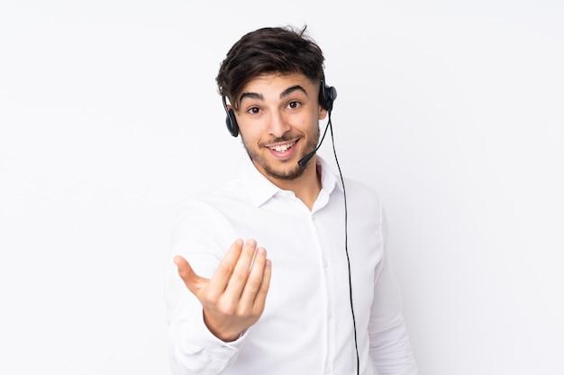 Telemarketer hombre árabe que trabaja con un auricular en la pared blanca invitando a venir
