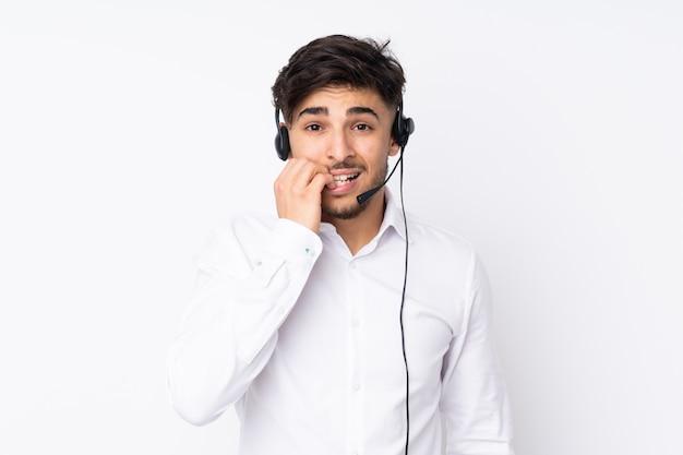 Telemarketer hombre árabe que trabaja con un auricular en la pared blanca nervioso y asustado