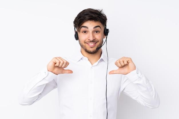 Telemarketer hombre árabe que trabaja con un auricular en la pared blanca orgulloso y satisfecho de sí mismo