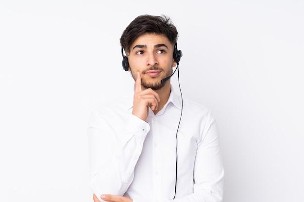 Telemarketer hombre árabe que trabaja con un auricular en la pared blanca pensando una idea